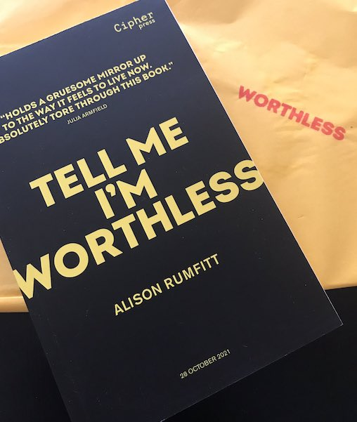 Proof copy of Tell Me I'm Worthless with yellow text on a black background and yellow tissue paper with a red stamp saying 'worthless'.